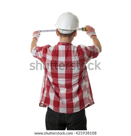 Cute teenager boy in red checkered shirt, building helmet and measuring tape standing from back  over white isolated background, half body, constructing concept - stock photo
