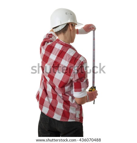 Cute teenager boy in red checkered shirt, building helmet and measuring tape standing from back  over white isolated background, half body, constructing concept