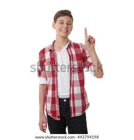 Cute teenager boy in red checkered shirt pointing up over white isolated background, half body
