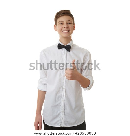 Cute teenager boy in white shirt and black bow tie showing thumb up sign over white isolated background, half body - stock photo