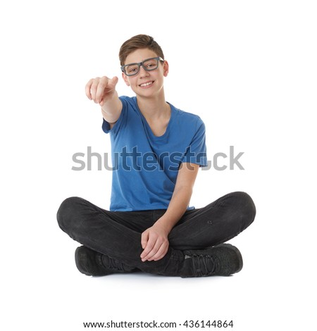 Cute teenager boy pointing up in blue T-shirt, glasses and lotus posture over white isolated background - stock photo