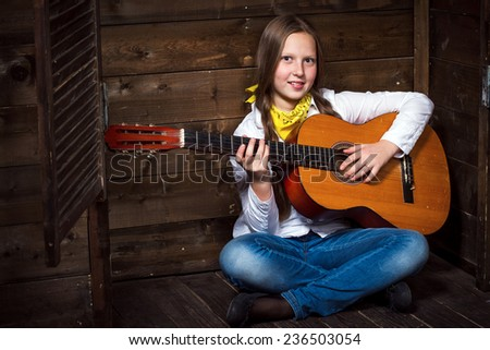 Cute teenager cowgirl on a ranch and plays the guitar - stock photo