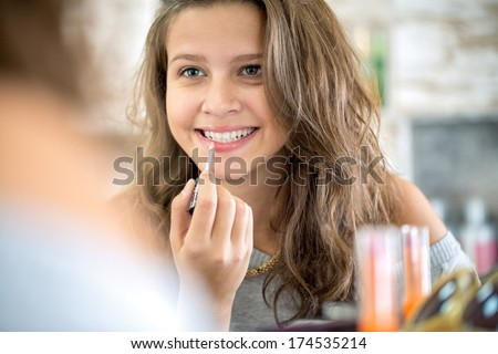 Cute teenager girl applying  lip gloss, make up front mirror  - stock photo