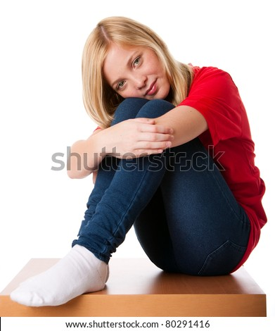 Cute teenager girl feeling lonely sitting alone with knees pulled up and arms around legs, isolated.