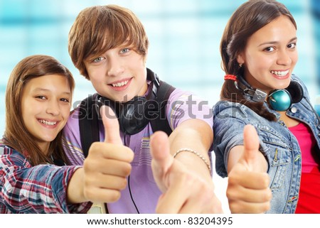 Cute teens with headphones showing thumbs up and smiling at camera