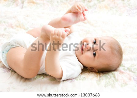 Cute ten month baby on bed. Low DOF [Approx. 10 mos] - stock photo