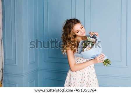 Cute tender blond girl standing in a studio with blue walls and holding a bouquet of flowers in her hands. She wears white dress and smiles. Flowers are wrapped in blue paper. - stock photo