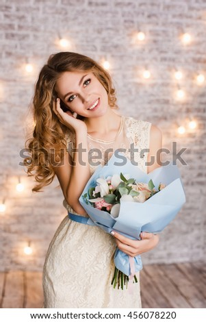 Cute tender slim girl with blond curly hair standing in a studio with white background with flashlights. She smiles and looks sweet. She has her arm in hair and holds a blue bouquet of flowers. - stock photo