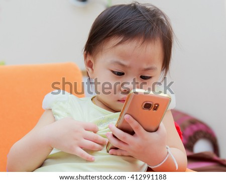 Cute thai Baby Playing with Phone on sofa - stock photo