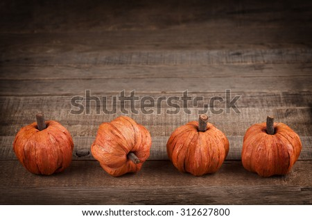 Cute Thanksgiving Mini Pumpkins made of fibers in row at bottom of rustic wood board background with room or space for copy, text, your words. Horizontal with dark, dramatic vignette for mood. - stock photo
