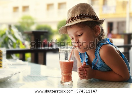 Cute thinking kid girl drinking tasty juice in street restaurant