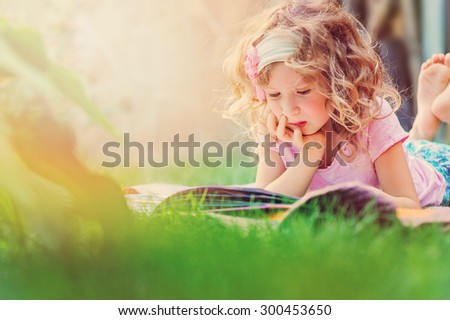 cute thoughtful child girl reading book in summer garden - stock photo