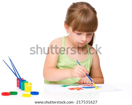 Cute thoughtful child play with paints while sitting at table, isolated over white