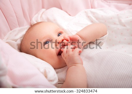 Cute three month baby girl laying in a bassinette - stock photo