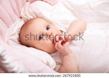Cute three month baby girl laying in a bassinette looking at camera - stock photo
