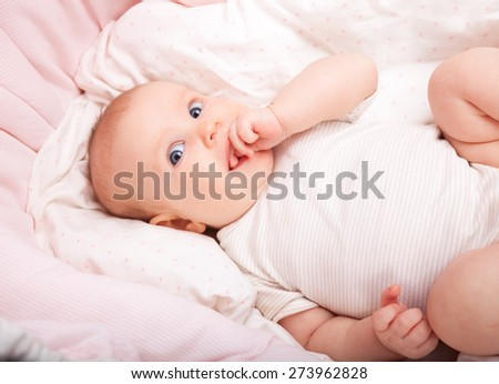 Cute three month baby girl laying in a bassinette looking at camera sucking hand - stock photo
