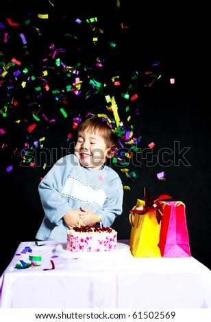 cute three year old baby celebrating his birthday and blowing off the candles on the cake - stock photo