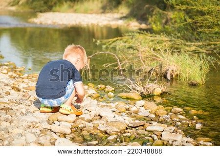 Cute three year old boy throwing stones to the water outdoor on a summer day.Little  on the river bank.Kids Games, river, childhood, pebbles, carefree, fun - the concept of children to play outdoors. - stock photo