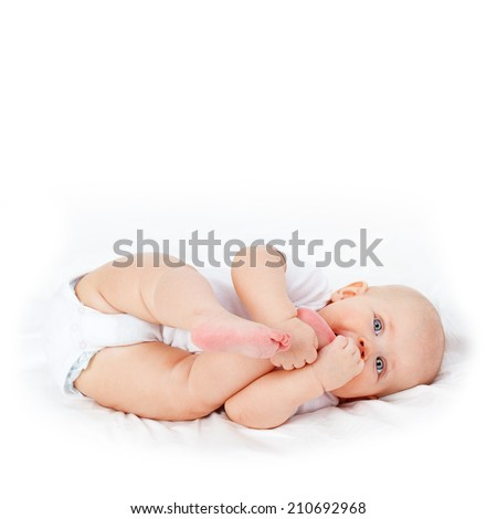 Cute tiny blue eyed baby lying on soft white cover. Beautiful sweet newborn girl biting her legs. - stock photo