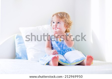 Cute toddler, adorable curly little girl in a blue dress, sitting on a bed reading a book playing in a sunny white bedroom  - stock photo