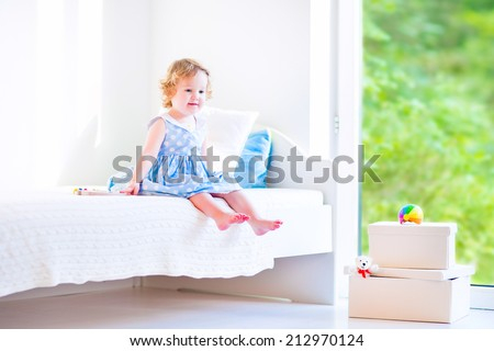 Cute toddler, adorable curly little girl in a blue dress, sitting on a bed reading a book playing in a sunny white bedroom with toy boxes and big garden view window - stock photo