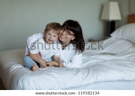 Cute toddler and pretty mom in bed - stock photo
