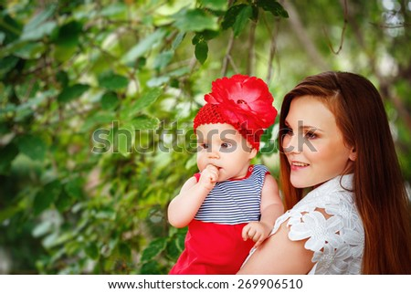 Cute Toddler Baby Girl in REd Dress sitting on Mom`s Hands. Relaxing in green summer Park. - stock photo