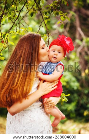 Cute Toddler Baby Girl sitting on Mom`s Hands, looking into camera. Mother kissing the Child. Relaxing in green summer Park. - stock photo