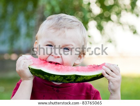 Cute toddler blonde boy is eating watermelon