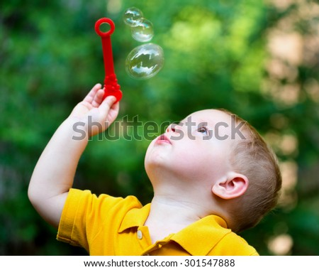 cute toddler boy blowing soap bubbles - stock photo