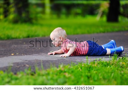 Cute toddler boy fell on park road