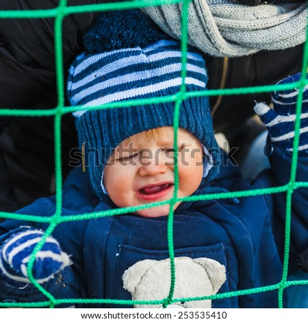 Cute Toddler Boy Is Unhappy Caught in the Net - stock photo