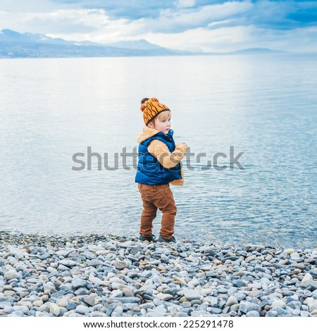 Cute toddler boy playing next to lake on a cold day - stock photo