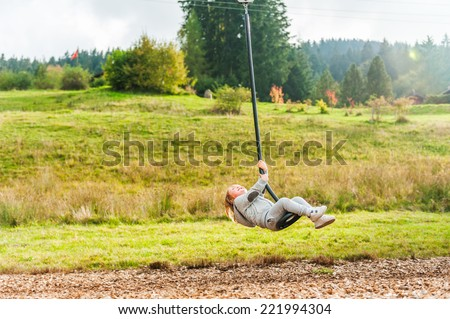 Cute toddler boy playing on a chain swing, having fun in a park on a nice autumn day - stock photo
