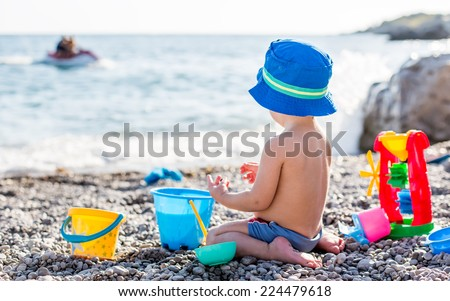 cute toddler boy playing on the beach  - stock photo