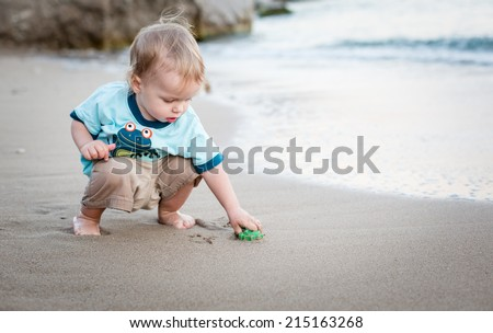 cute toddler boy playing on the beach at sunset - stock photo