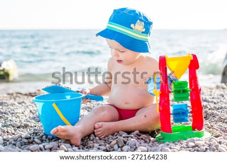 cute toddler boy playing on the beach in summer - stock photo