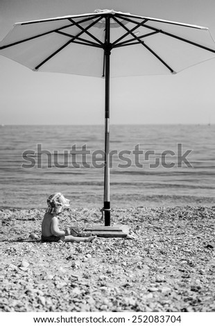 cute toddler boy playing on the beach under an umbrella ( black and white ) - stock photo