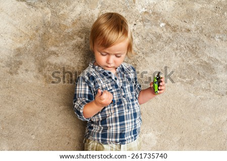 Cute toddler boy playing with toy cars outdoors - stock photo