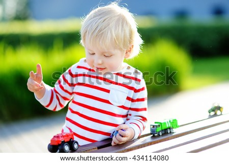Cute toddler boy playing with toy cars outdoors at warm summer day - stock photo