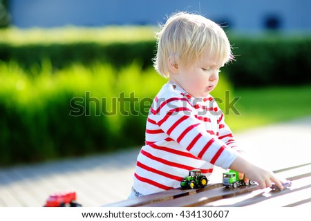 Cute toddler boy playing with toy cars outdoors at warm summer day