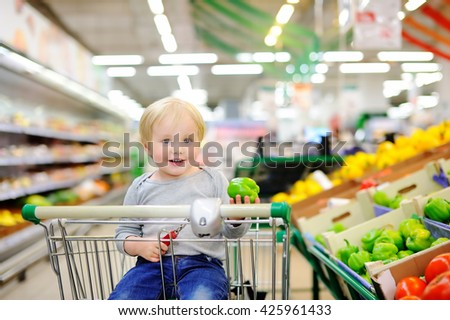 Cute toddler boy sitting in the shopping cart in a food store or a supermarket