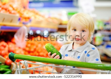 Cute toddler boy sitting in the shopping cart in a food store or a supermarket. Healthy lifestyle for young family with kids