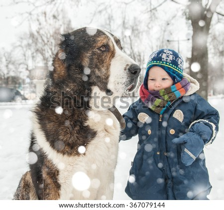 Cute toddler child boy and big dog together in winter nature