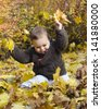 Cute toddler child playing with yellow autumn or fall leaves. - stock photo