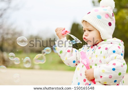 cute toddler girl blowing   soap bubbles - stock photo