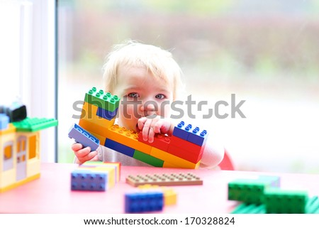 Cute toddler girl building house from plastic blocks sitting next to a big window  - stock photo