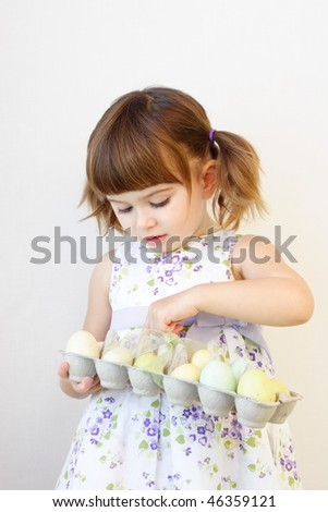 Cute toddler girl counting Easter eggs in the carton box - stock photo
