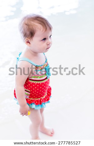 Cute toddler girl enjoying playing in the water in indoor swimming pool.