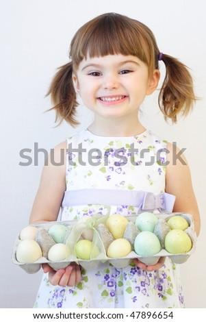 Cute toddler girl holding a carton of Easter eggs - stock photo